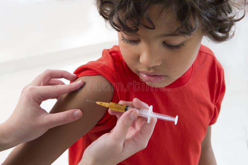 接受在胳膊的男孩疫苗 库存图片