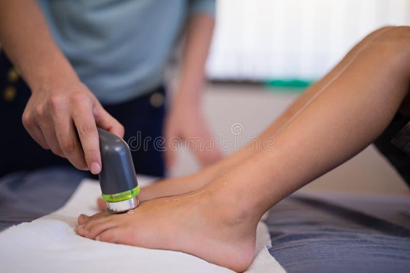 接受在脚的男孩的低部分超声波扫描从女性治疗师 库存图片