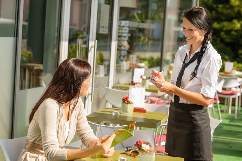 接受妇女的命令的女服务员在咖啡馆棒 图库摄影