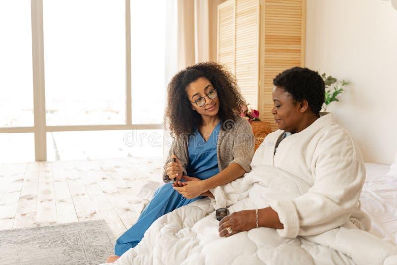 接受妇女的护士戴着眼镜验血有糖尿病的 库存图片