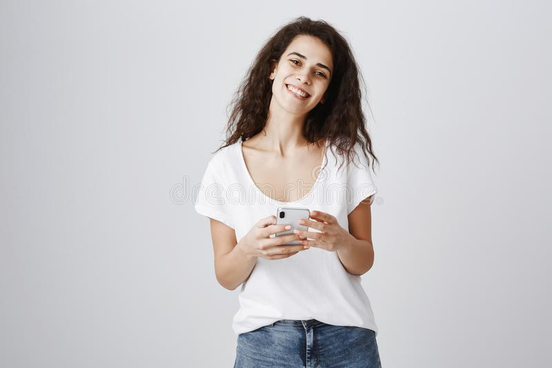 接受恭维,当站立在队列浏览在智能手机时的美丽的女孩 可爱的时髦的卷发的妇女 免版税图库摄影