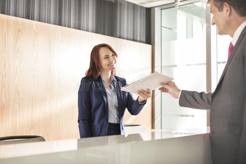 接受文件的商人从接待员在办公室 免版税图库摄影