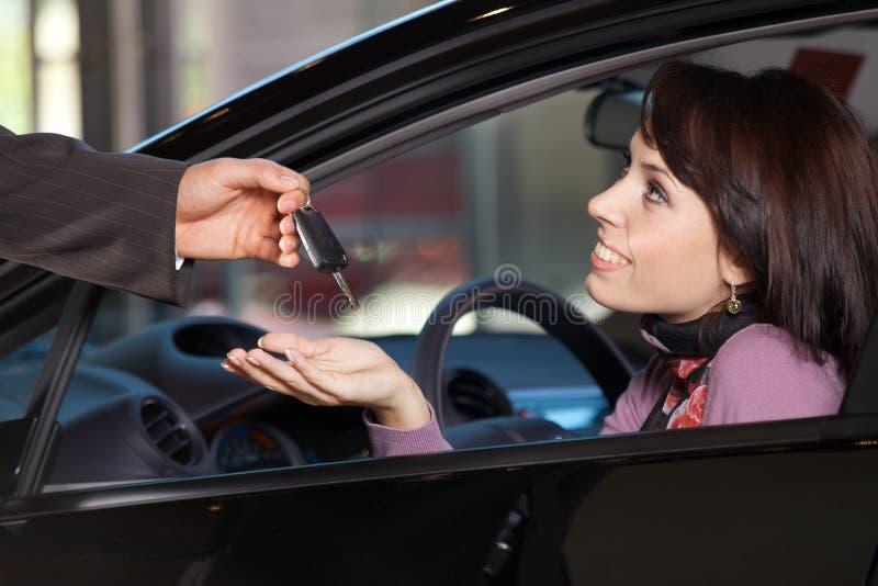 接受汽车钥匙的少妇从汽车推销员 免版税库存照片