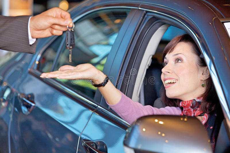 接受汽车钥匙的少妇从汽车推销员 图库摄影