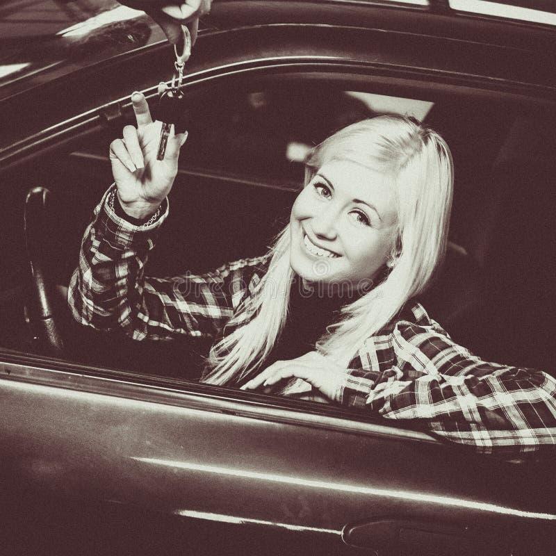 接受汽车钥匙的微笑的少妇单色画象对半新车 图库摄影