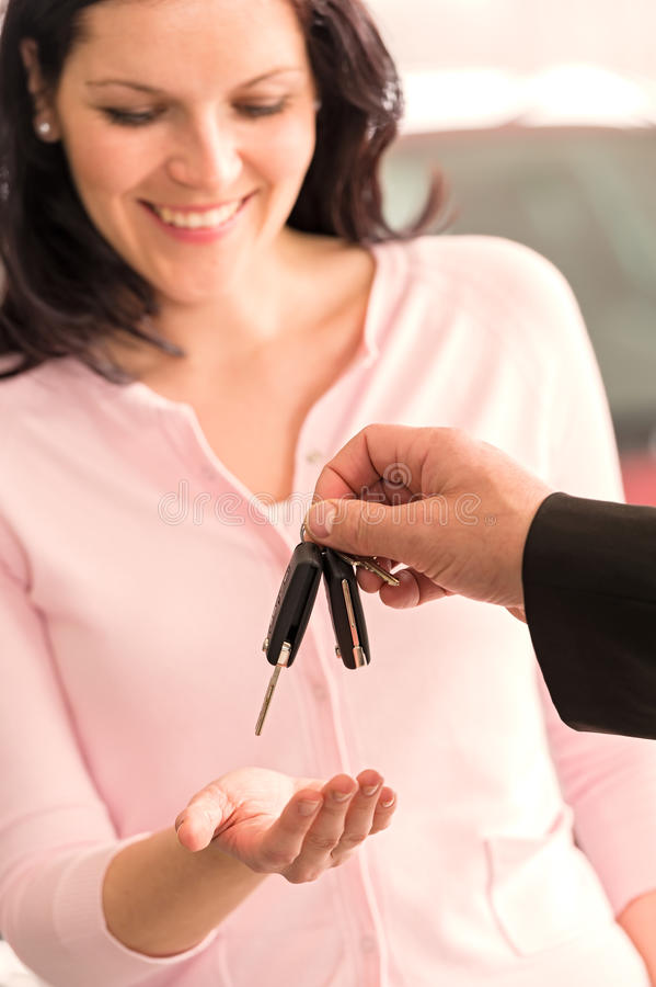 接受汽车钥匙的愉快的妇女从代理 图库摄影