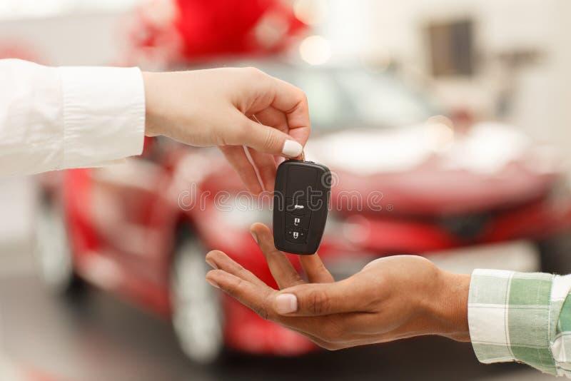 接受汽车钥匙的非洲人从女推销员 库存图片