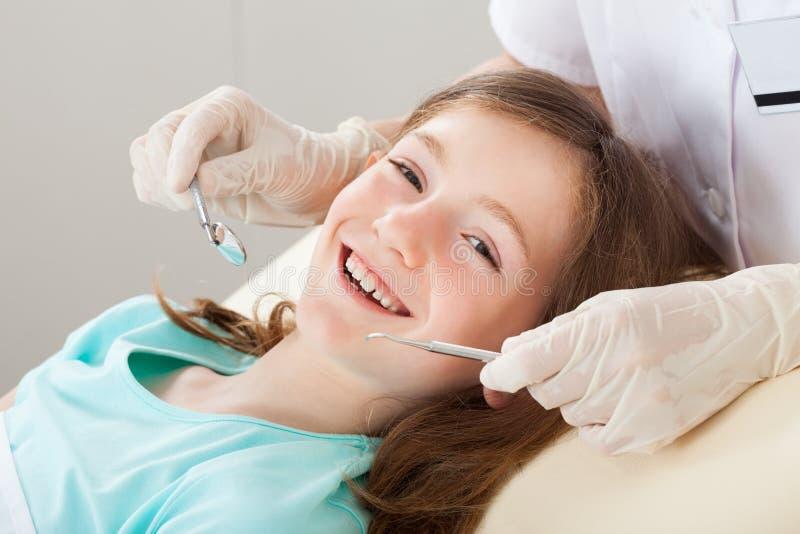 接受牙齿治疗的愉快的女孩 库存图片