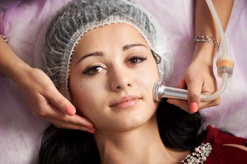 接受电ultrusound面部按摩的特写镜头妇女在美容院 免版税库存照片