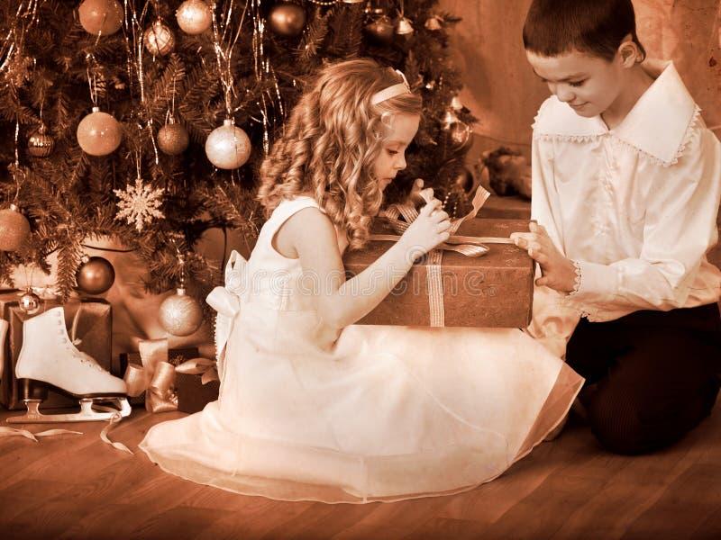 接受礼品的子项在圣诞树下。 图库摄影