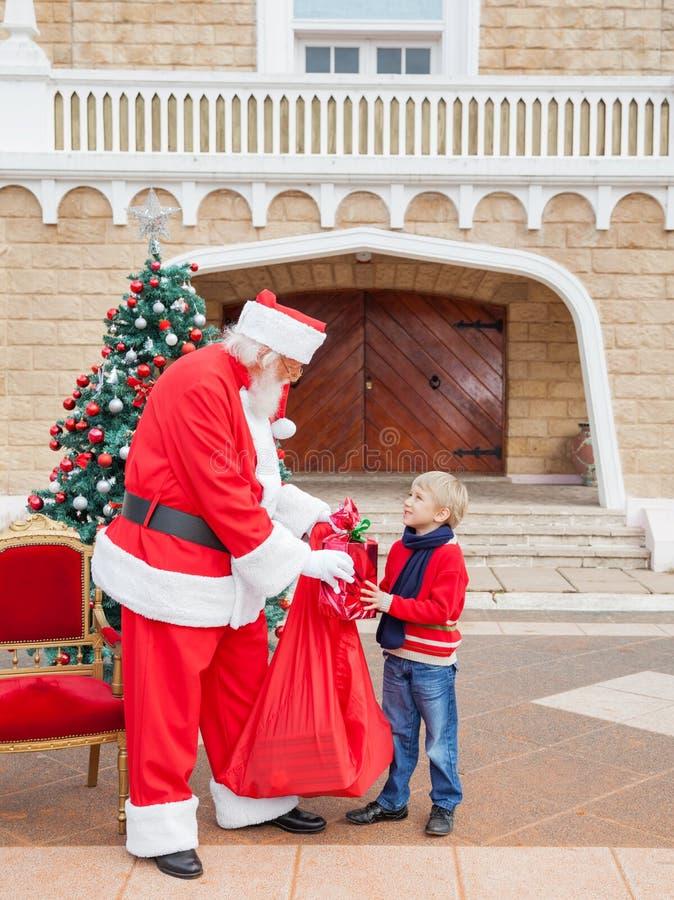 接受礼物的男孩从圣诞老人 库存照片