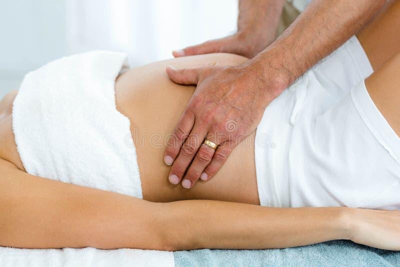 接受胃按摩的孕妇从男按摩师 免版税库存图片