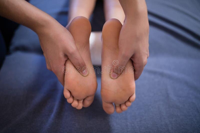 接受脚按摩的男孩特写镜头从在床上的女性治疗师 免版税库存照片