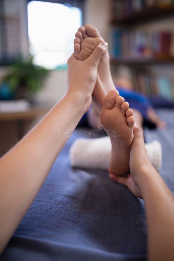接受脚按摩的男孩特写镜头从年轻女性治疗师 库存图片
