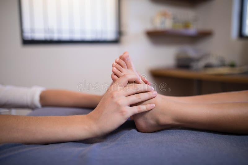 接受脚按摩的男孩的低部分从女性治疗师 库存照片