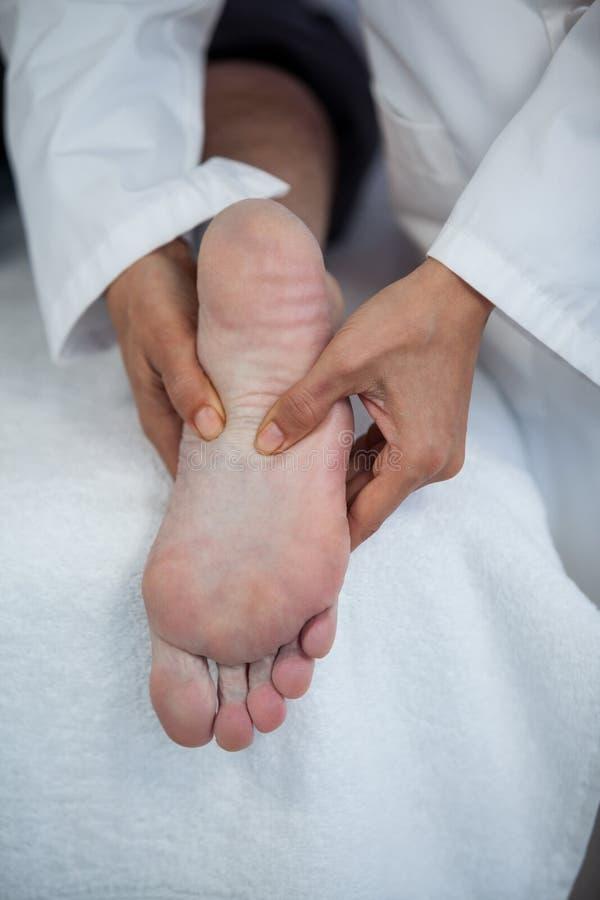接受脚按摩的老人从生理治疗师 免版税库存照片