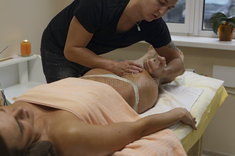 接受身体按摩的浅黑肤色的男人适合的妇女客户在温泉俱乐部  图库摄影