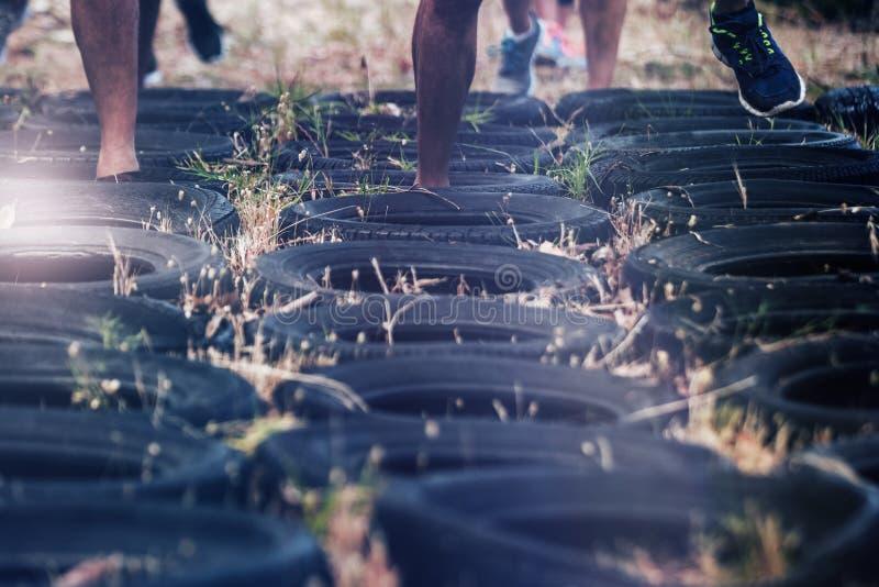 接受轮胎障碍桩训练的人的低部分 图库摄影