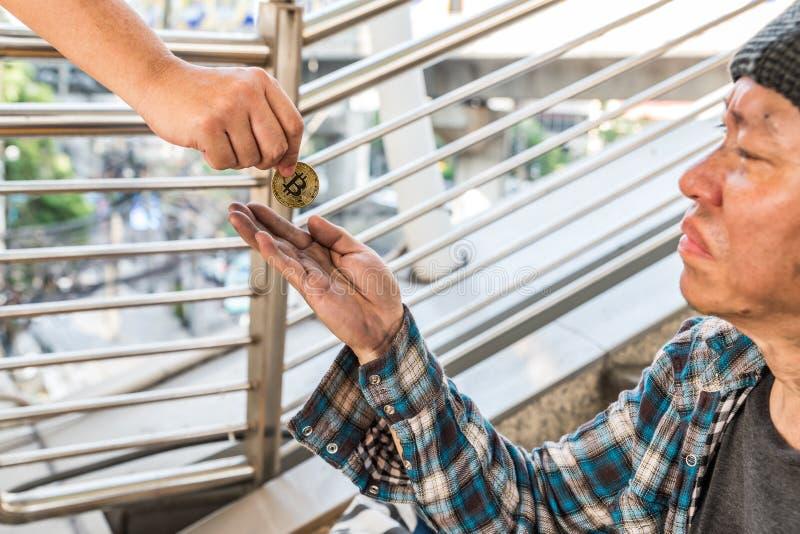 接受金bitcoin硬币的一个男性无家可归的叫化子 库存照片