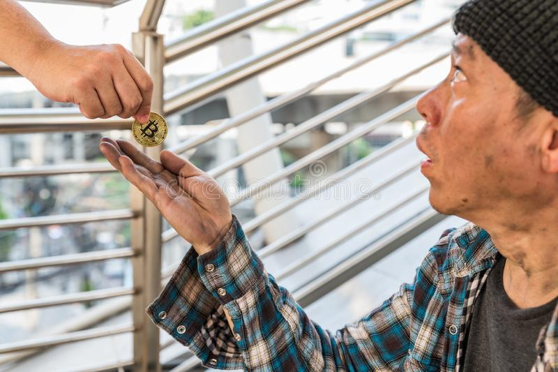 接受金bitcoin硬币的一个男性无家可归的叫化子 免版税库存图片