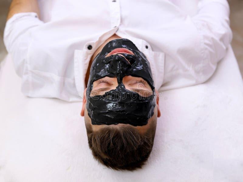 接受面部黑面具的人的温泉疗法 免版税库存图片