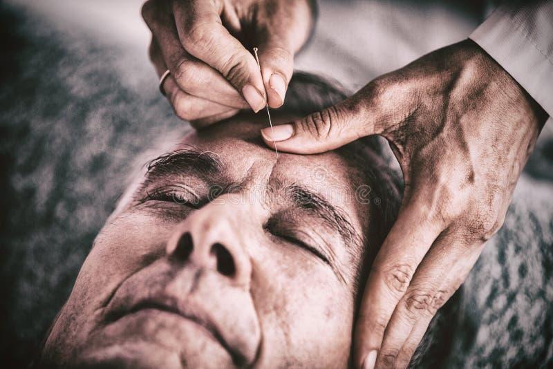 接受顶头按摩的老人从生理治疗师 库存照片
