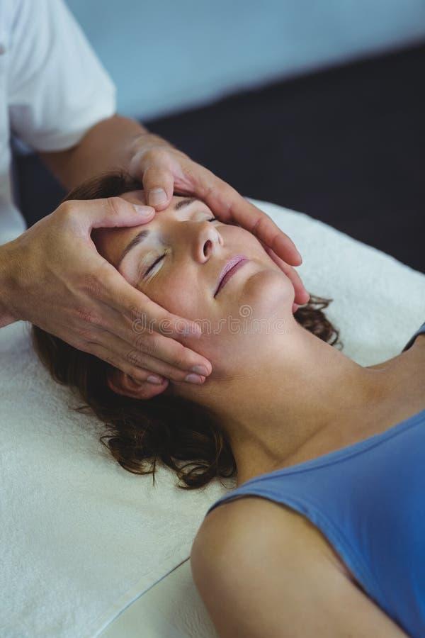 接受顶头按摩的妇女从生理治疗师 图库摄影