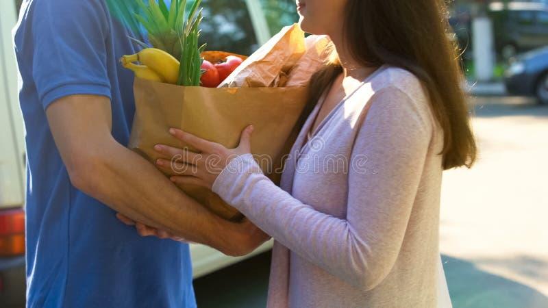 接受食品杂货袋的微笑的妇女从交付工作者,超级市场服务 免版税库存图片