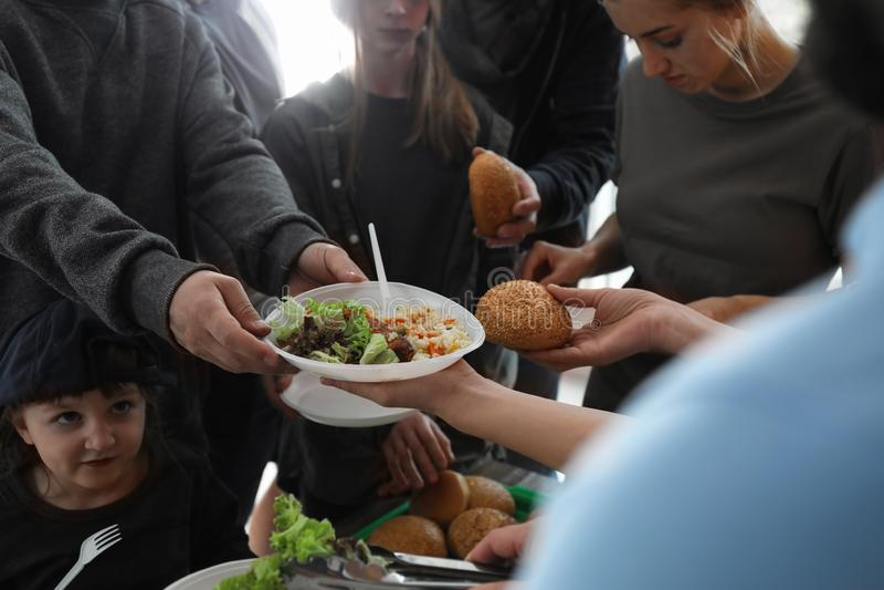 接受食物的可怜的人民从志愿者户内 免版税库存图片