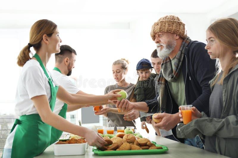 接受食物的可怜的人民从志愿者 库存照片