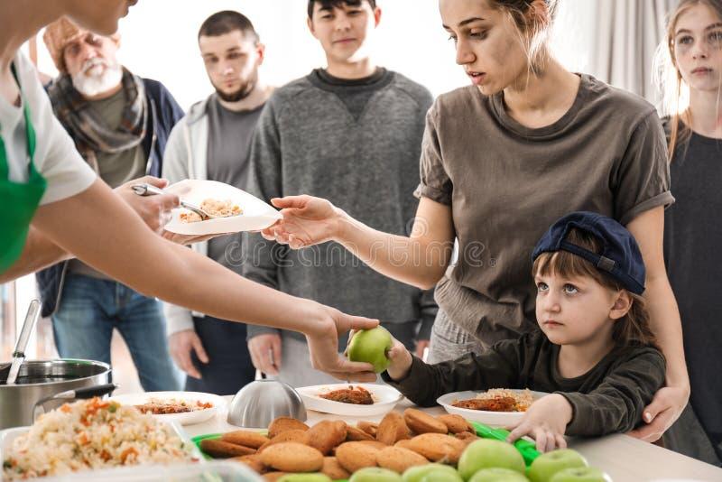 接受食物的可怜的人民从志愿者 免版税库存图片