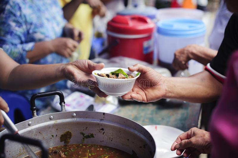 接受食物的可怜的人民从捐赠:无家可归的人帮助与救济粮食,饥荒安心:给食物的志愿者 免版税库存照片