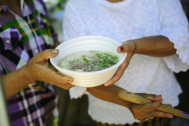 接受食物的可怜的人民从捐赠:无家可归的人帮助与救济粮食,饥荒安心:给食物的志愿者 库存图片