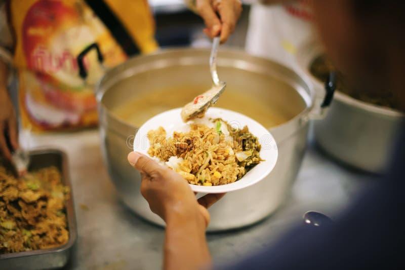 接受食物的可怜的人民从捐赠:社会分享的概念 免版税库存图片