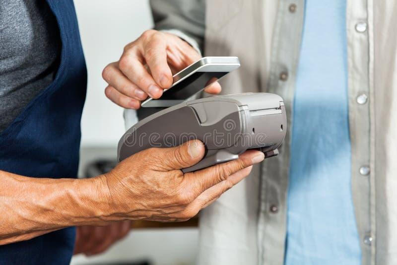 接受付款的推销员通过NFC技术 免版税库存照片