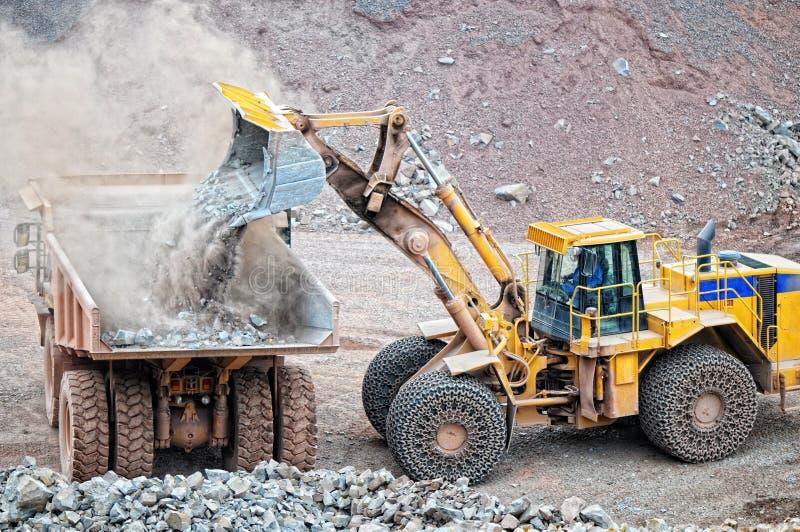 接地装载倾销者卡车的搬家工人用斑岩岩石在矿 库存照片