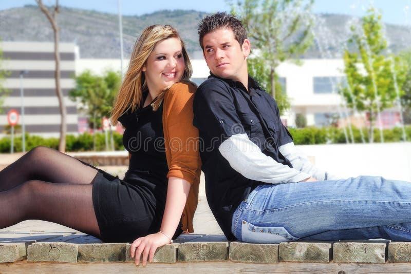 紧接坐在公园的年轻夫妇 免版税库存照片