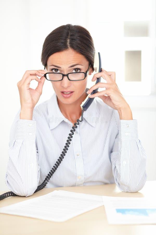 年轻接待员交谈在电话 库存照片