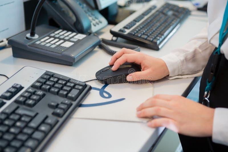 接待员递使用计算机老鼠在书桌在机场 免版税图库摄影