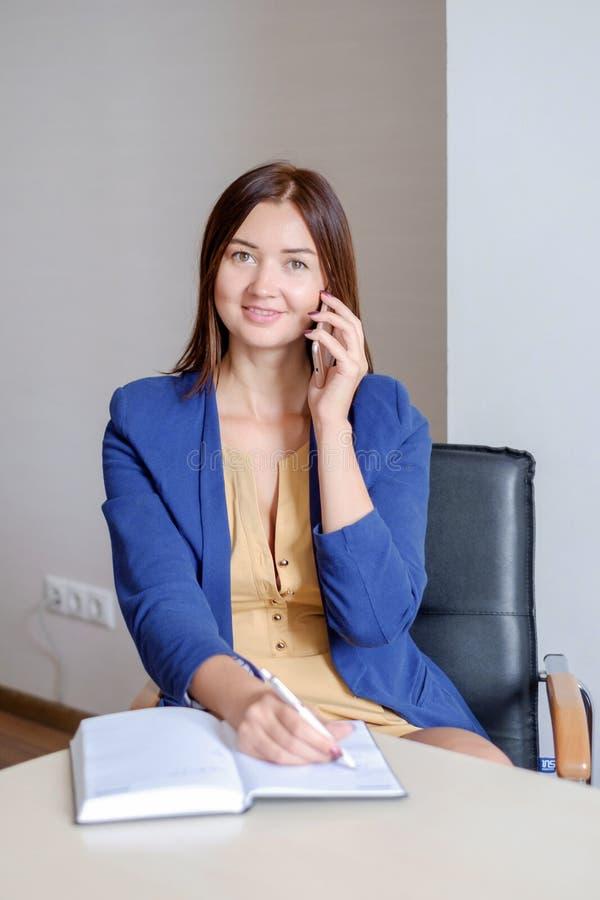 接手机电话和写笔记的便衣的女实业家入日历在办公桌 免版税库存照片