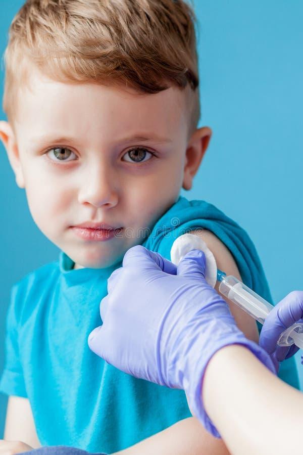 接种概念 女性医生接种逗人喜爱蓝色背景的,特写镜头小男孩 库存图片