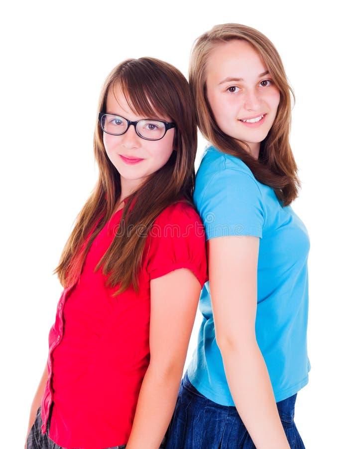 紧接站立两个青少年的女孩画象  免版税库存图片