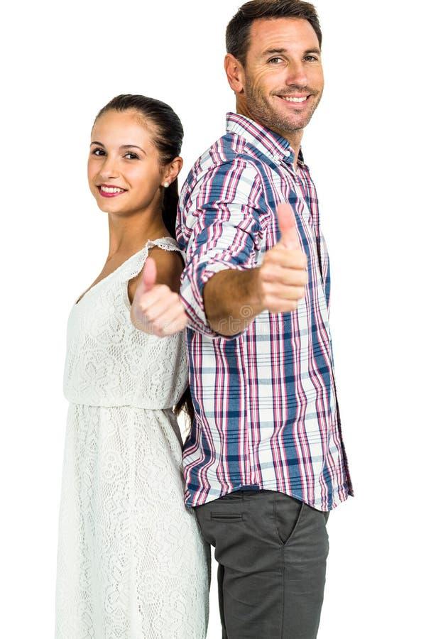 紧接站立微笑的夫妇显示赞许 库存照片