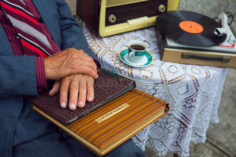 接触一本老象册的老人的手 免版税库存图片