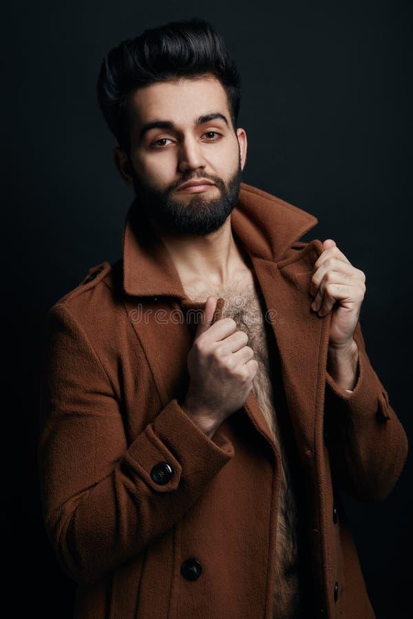 接触他的外套衣领和摆在照相机的时髦的强壮男子 免版税图库摄影