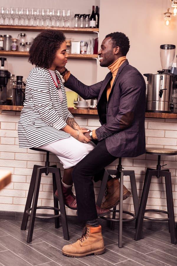 接触他的女朋友面颊的愉快的年轻人 免版税图库摄影