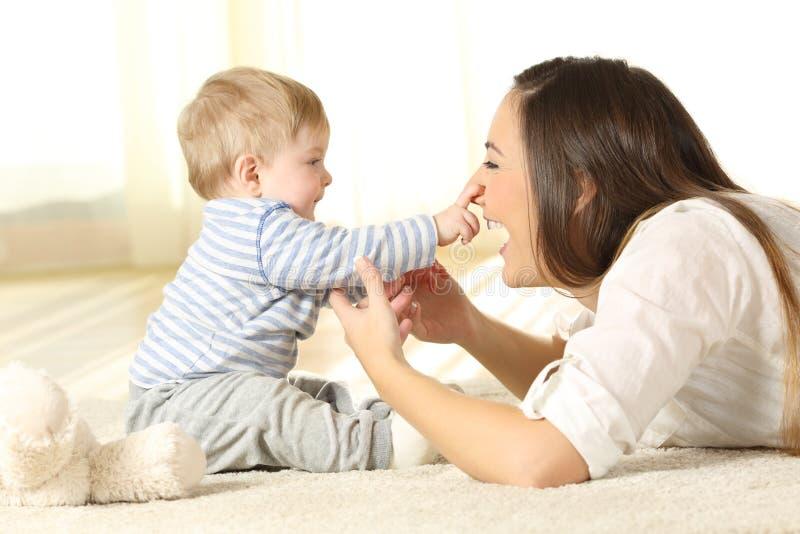 接触他的母亲面孔的愉快的婴孩 免版税库存图片