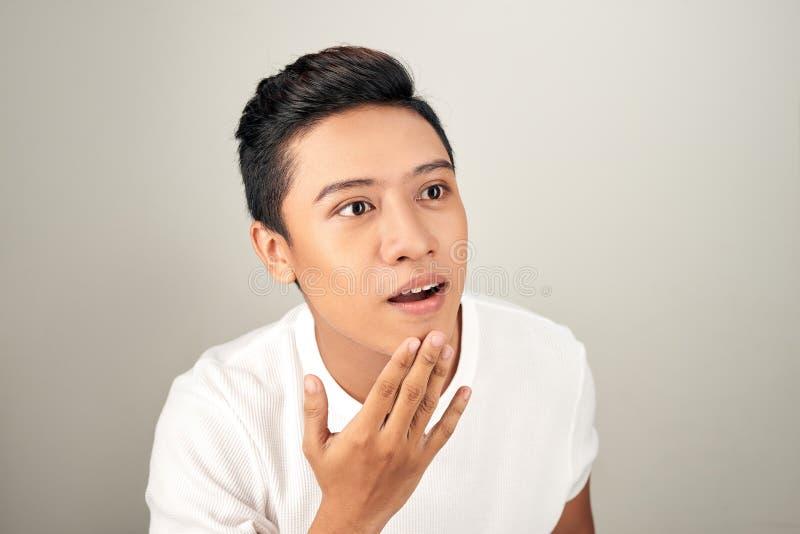 接触他的画象演播室的英俊的亚裔人面孔关闭白色背景的 库存图片