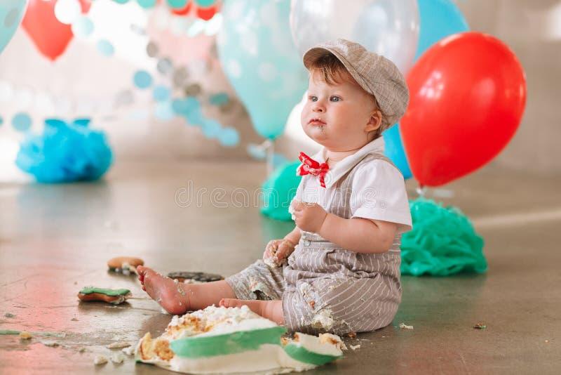 接触他的第一生日蛋糕的男婴 做杂乱cakesmash在装饰的演播室地点 肮脏的赤脚 免版税库存照片