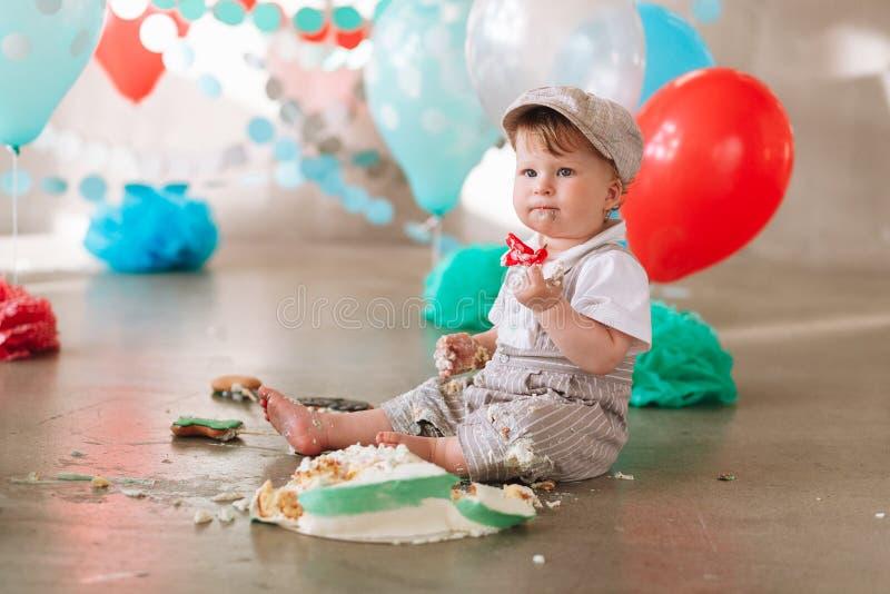 接触他的第一生日蛋糕的男婴 做杂乱cakesmash在装饰的演播室地点 肮脏的赤脚 免版税库存图片